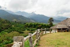 Sceniczny krajobraz na górach, drewnianym ogrodzeniu na przedpolu i domach na tle, Obraz Royalty Free