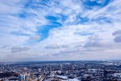 Sceniczny obrazek miasto w zimie antena, jasny niebieskie niebo z bielem chmurnieje pod śniegiem, wieżowów domy z dachami, obraz stock