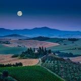 Sceniczny Tuscany krajobraz z tocznymi wzgórzami pod księżyc w pełni fotografia stock