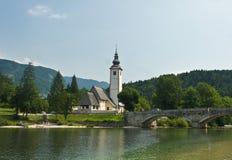 Sceniczny widok kościół St John baptysta, most, Juliańscy Alps i jezioro, Bohinj, Slovenia obraz royalty free