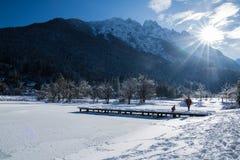 Sceniczny widok na cudownym marznącym jeziornym jasna z footbridge w julian alps w niebieskim niebie, kranjska gora, Slovenia Zdjęcia Stock