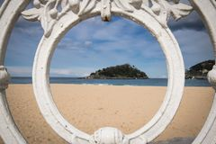 Sceniczny widok na isand Santa Clara od San Sebastian concha plaży przez ornamentacyjnej bielu żelaza ogrodzenia ramy, baskijski  Obraz Stock