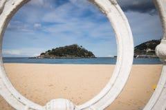 Sceniczny widok na isand Santa Clara od San Sebastian concha plaży przez ornamentacyjnej bielu żelaza ogrodzenia ramy, baskijski  Zdjęcie Royalty Free