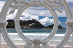 Sceniczny widok na San Sebastian plaży z wzgórza monte igueldo i Santa Clara wyspie przez ornamentacyjnej bielu żelaza ogrodzenia Obrazy Royalty Free
