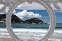 Sceniczny widok na San Sebastian plaży z wzgórza monte igueldo i Santa Clara wyspie przez ornamentacyjnej bielu żelaza ogrodzenia Fotografia Royalty Free