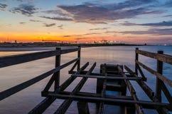 Sceniczny widok nad żurawiami i zbiornika portem Pointe-Noire od drewnianego mola z spokojnym morzem podczas czerwonego zmierzchu Zdjęcie Royalty Free