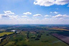 Scenisk fågelperspektiv av jordbruksmark i bygden, blå himmel med vita moln, fält med grönt gräs och träd, sjöar och arkivfoto