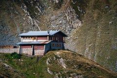 Scenisk landskapsikt på ett ensamt hus upptill av berget Transfagarasan, hotell, Rumänien arkivfoto