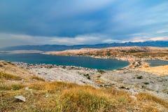 Scenisk sikt över by på Pag-ön i aftonen arkivfoton