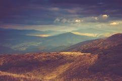 Scenisk sikt av berg, höstlandskap med färgrika kullar på solnedgången fotografering för bildbyråer