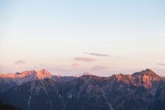 Scenisk sikt av bergpanorama med Alpenglow i aftonen Royaltyfri Foto