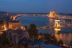 Scenisk sikt av den Budapest staden på den blåa timmen med den upplysta kedjebron, den ungerska parlament- och Donauinvallningen royaltyfria foton