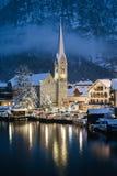 Scenisk sikt av den gamla kyrkan i ljus i vintertid, Hallstatt, A royaltyfri bild