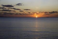 Scenisk sikt av den härliga solnedgången ovanför havet med moln Arkivfoto