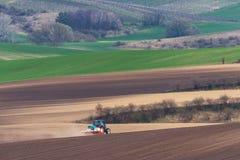 Scenisk sikt av den moderna lantbruktraktoren som som plogar det bruna fältet Traktor som odlar fältet Liten blå traktor med röd  Fotografering för Bildbyråer