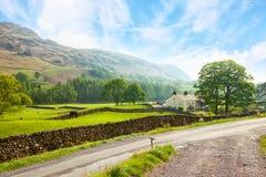 Scenisk sikt av en dal med en landsväg i förgrunden på den soliga dagen i sjöområdesnationalparken, Cumbria, England, U royaltyfri fotografi