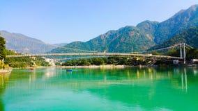 Scenisk sikt av Ganges River som flödar till och med berg arkivfoto