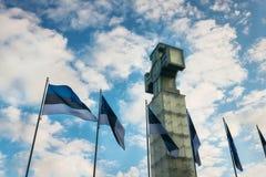 Scenisk sikt av korset av Liberty Vabadusrist och estonian flaggor på solnedgången arkivbilder