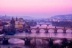 Scenisk sikt av Prague broar och cityscape på soluppgång Arkivfoto