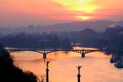 Scenisk sikt av soluppgång över floden och den av broar för Prague ` s Royaltyfria Bilder