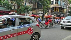 Scenisk sikt av upptagen trafik i Hanoi den gamla fjärdedelen med många mopeder och medel lager videofilmer