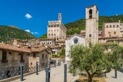 Scenisk sikt i Gubbio med den Palazzo deien Consoli och kyrkan av Giovanni Battista, medeltida stad i Umbria arkivfoton