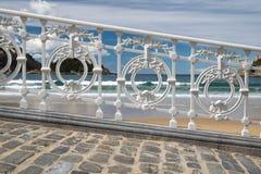 Scenisk sikt på den San Sebastian stranden i conchafjärd till och med det dekorativa vita järnstaketet, basque land, Spanien Arkivbilder