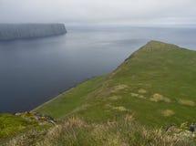 Scenisk sikt på kanten av klippan från överkanten av branta konung- och för drottning Hornbjarg klippor i västra fjordar, avlägse royaltyfria bilder