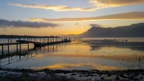 Scenisk sjöinställning med bryggan på solnedgången royaltyfria bilder