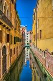 Scenisk smal kanal med gula väggar på solig dag, Venedig, Italien arkivbilder