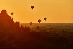 Scenisk soluppgång med många ballonger för varm luft ovanför Bagan i Myanmar Arkivbild