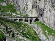 Scenisk stenig stångbro i schweiziska fjällängar i SCHWEIZ nära den Andermatt staden Royaltyfria Foton