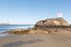 Scenisk strand, Long Island Sound med varningstecknet Royaltyfri Foto