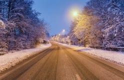 Scenisk tom vintrig väg på aftonen Royaltyfria Bilder