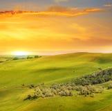 Sceniska fält, kullar och soluppgång Royaltyfria Bilder