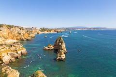 Sceniska klippor och grottor undersöker vid turister med kajaker och fartyg i Algarve, Portugal arkivfoto