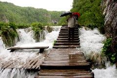 Sceniska vattenfall och strandpromenad i Plitvice sjönationalpark, när det regnar Arkivfoto
