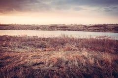 Sceniskt höstlandskap under gryning på flodbanken i lantligt fält royaltyfri foto
