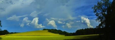 Sceniskt landskap med stormmolnet i bakgrund över gröna åkerbruka fält royaltyfria bilder