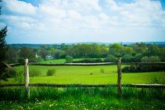 Sceniskt lantligt landskap som presenterar frodig jordbruksmark och staketet i Surr Fotografering för Bildbyråer
