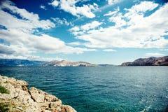 Sceniskt sjösidalandskap med klippor och havvågor, lugna vatten och molniga himlar Mjuk tappningeffekt på fotoet Arkivfoto