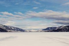 Sceniskt vinterlandskap med sjön, berg och himmel Royaltyfri Foto