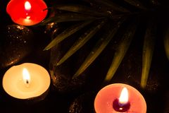 Scent colorful lighted candles on black wet stones and green leaf with droplets, dark photography.  Stock Photos