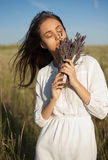 Scent of lavender. Portrait of a young brunette beauty enjoying the scent of lavender outdoors stock photo