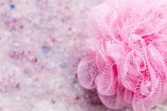 Scented bath salt with bath sponge closeup background in pink and purple colors, top view. Scented bath salt closeup background in pink and purple colors stock photography