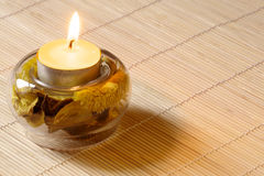 Scented candle. Burning scented candle witn dried flowers on wood mat Royalty Free Stock Photos