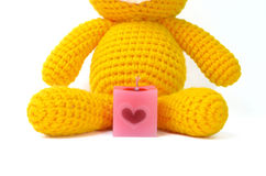 Scented candle and doll. Square pink scented candle and yellow knitting bear doll on white background Stock Photo