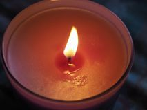 Scented candle flame. Red lit scented candle with flickering flame Stock Photography