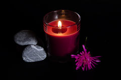 Scented candle. With flower and stones on a black background Stock Photos