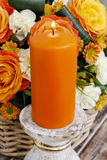 Scented candle in front of bouquet of  flowers Stock Images